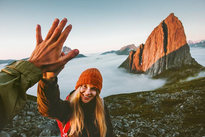mochileros chocando la mano en la cima de una montaña